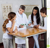 mature porn teacher teacher explaining molecular structures mature male students desk science lab student using computer classroom