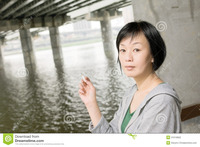 asian mature pics woman smoking closeup portrait mature asian under bridge city daytime stock photography