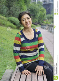 asian mature pics happy asian mature woman sitting bench outdoors stock photo