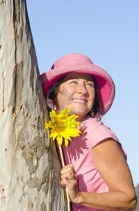 mature in sexy roboriginal portrait sexy mature woman wearing pink hat sunflower hugging tree park isolated blue photo