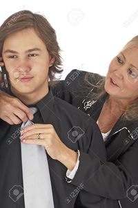 mature mom rcarner mature mother fixing sons necktie talks cellphone stock photo