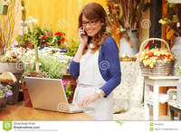 mature photos smiling mature woman florist small business flower shop owner using telephone laptop take orders store photos
