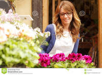 mature photos smiling mature woman florist small business flower shop owner shallow focus royalty free stock using telephone laptop take orders store