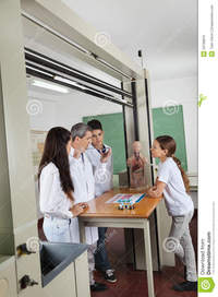 mature teacher teacher experimenting mature students looking him desk lab male student using computer classroom
