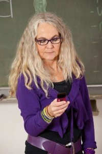 mature teacher fotosmurf mature teacher standing classroom sending text message photo