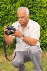 mature asian cabman mature asian photographer checking his camera settings photo