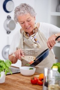 mature old logos mature old woman holding pan preparing food kitchen photo