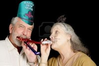 mature party lisafx mature couple year party hats blowing noise makers isolated black photo