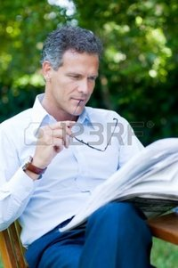 outdoor mature rido handsome mature man reading news outdoor break holding pair glasses photo
