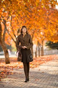 outdoor mature tankist happiness mature beautiful woman walking outdoor park autumnal day photo