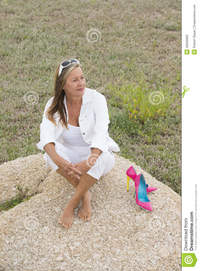 outdoor mature relaxed confident woman outdoor wth high heels portrait attractive mature sitting alone happy rock bare feet heel stock photo
