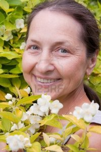 outdoor mature mature woman outdoor near blossoming bush jasmine photo