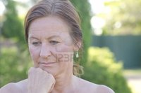 outdoor mature roboriginal outdoor portrait sad worried looking mature woman isolated blurred background photo