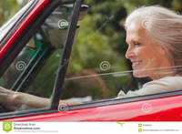 red mature smiling mature woman driving red convertible sunny day stock