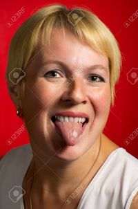 red mature shell mature woman showing tongue against red background stock photo