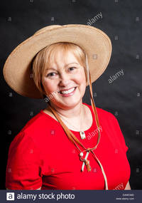 red mature comp eawcmd happy mature woman wearing red shirt cowgirl hat stock photo