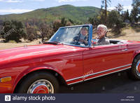 red mature comp npnk mature couple driving red convertible car along country road smiling stock photo