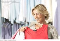 red mature photo mature blonde woman shopping clothes shop holding red vest coathanger smiling
