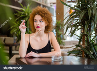 redhead mature stock photo thoughtful redhead woman curly hair smoking restaurant pic