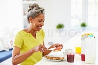 spreading mature preview mature woman eating breakfast spreading jam toast