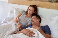wife mature warrengoldswain happy mature smiling husband wife couple looking mobile cell phone laying bed stock photo